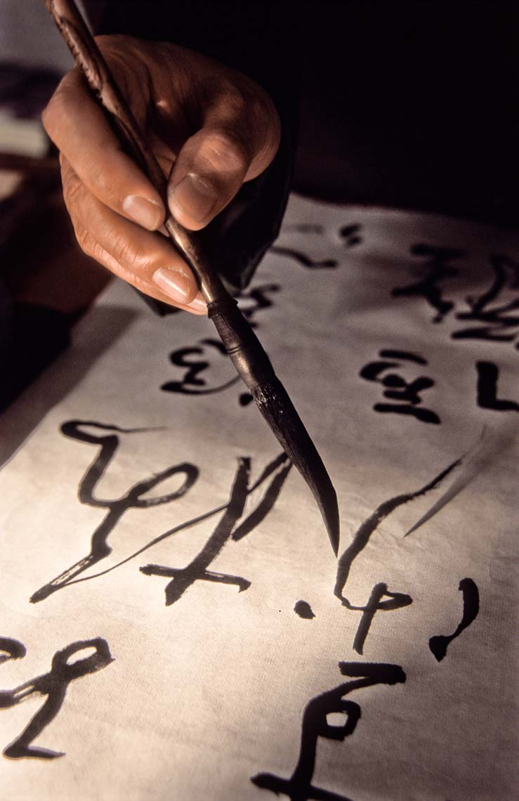 Calligrapher completing a work on paper.