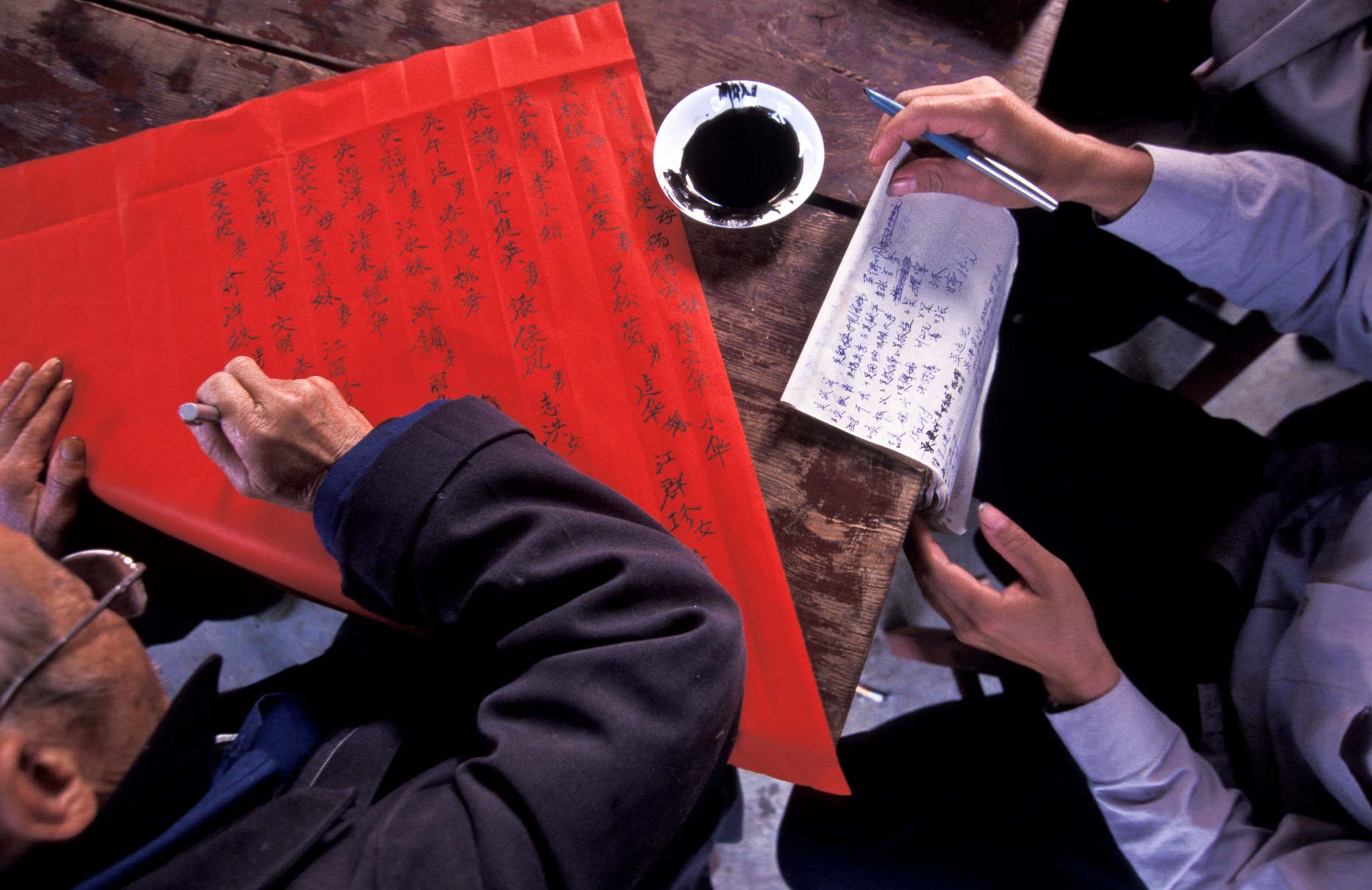 Elder man writing on a village notice board paper