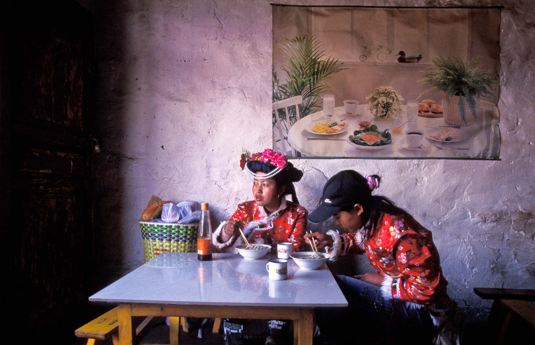 Two young Mo Su ethnic minority women having noodle lunch